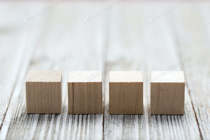 Four wooden toy cubes on grey wooden background