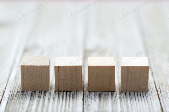 Vier Holzspielzeugwürfel auf grauem Holzhintergrund