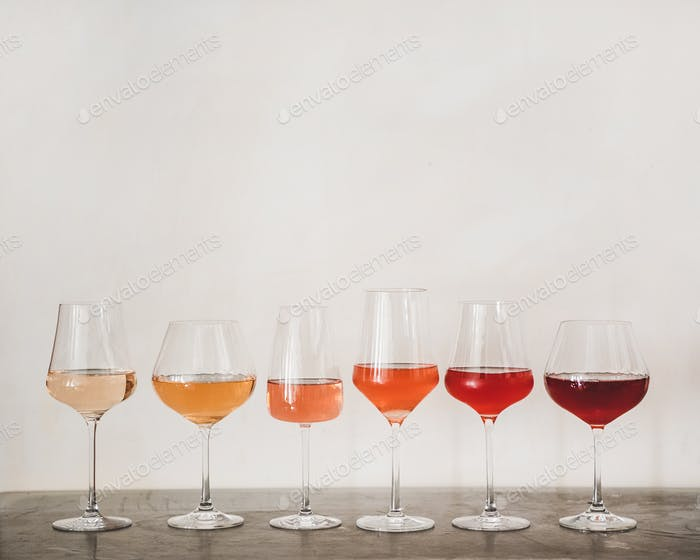 Various shades of Rose wine in glasses on concrete table