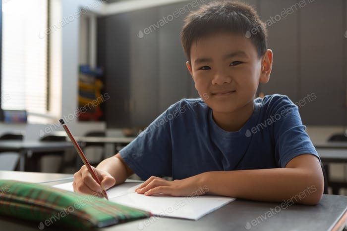 Schoolboy looking at camera in classroom at elementary school