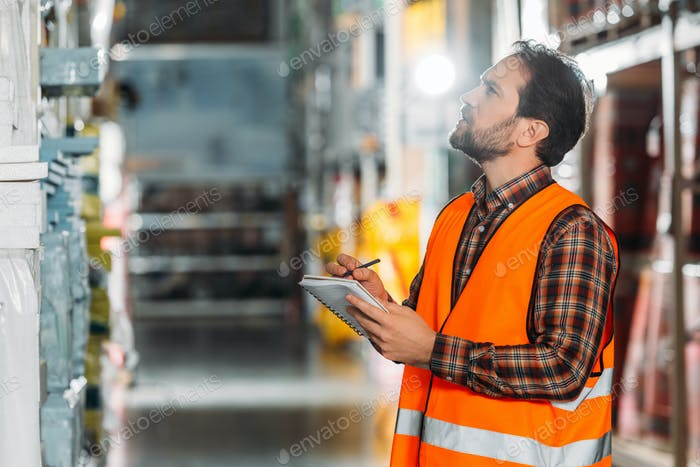 male worker in safety vest writing in notepad in storehouse