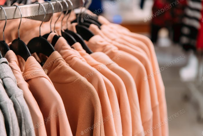 Many One-colour Hooded Sweatshirt On Hanger In Store Of Shopping