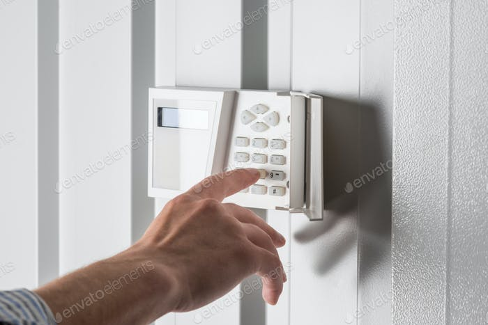 person typing on keypad of home security alarm, security system concept