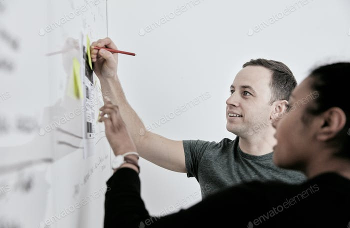 Man and woman discussing work and making notes on a whiteboard.  in an office.