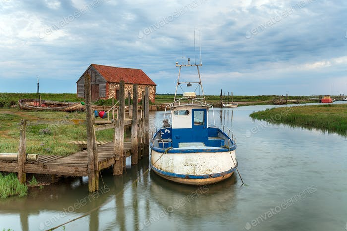 A fishing boat moored at a wodden jetty at Thornham
