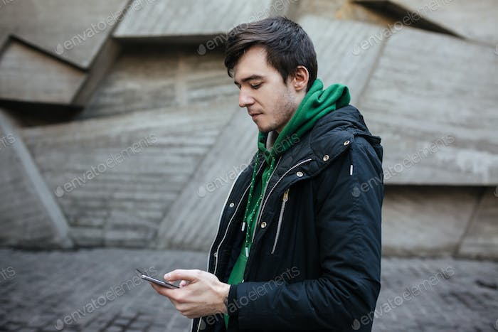 Young man with dark hair in black jacket standing on street with mobile phone in hands