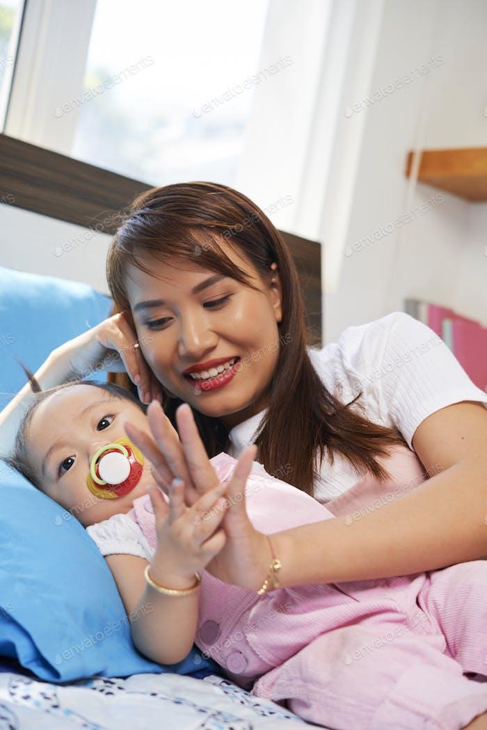 Junge Frau schaut kleine Tochter an
