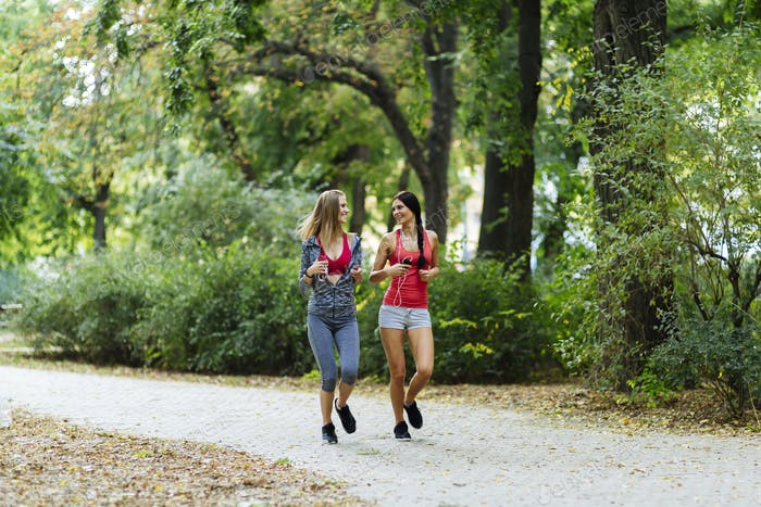 Two beautiful women jogging in park
