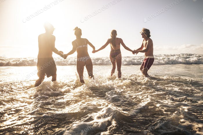 Group of friends enjoy summer holiday vacation at the beach running together in the sea water