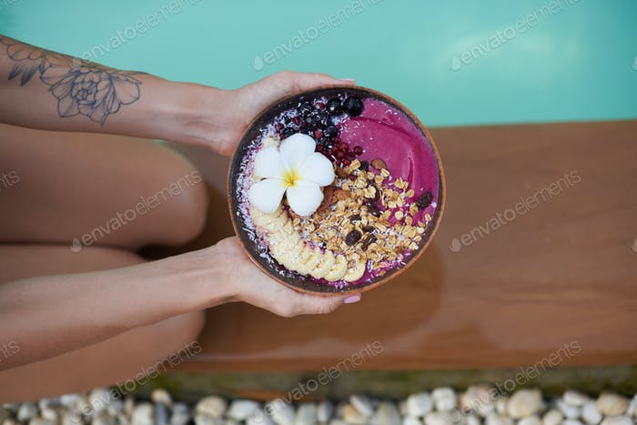 Tattooed woman holds a plate filled with asian natural food