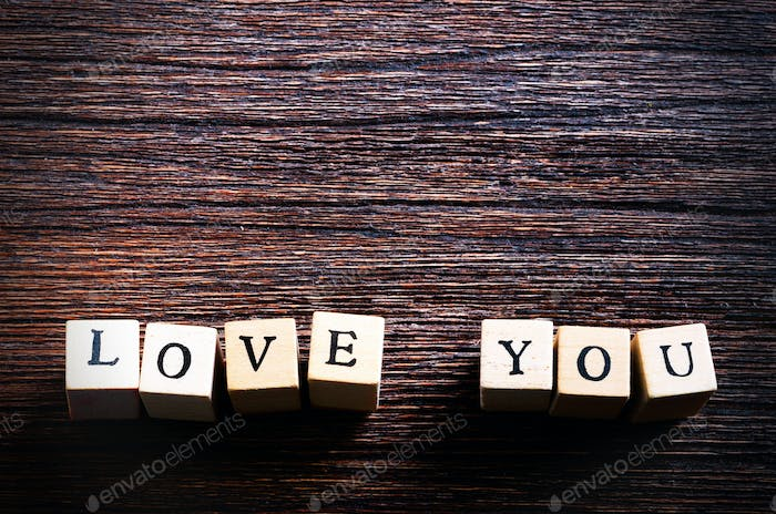 Wood cubes with inscription LOVE YOU on wooden background. Free space for your text