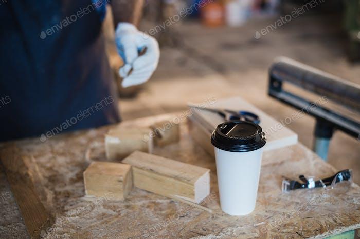 Moderner Tischlerarbeitsplatz mit Tablette, Kaffee, Schere und Holzteilen auf dem Tisch, in der Werkstatt