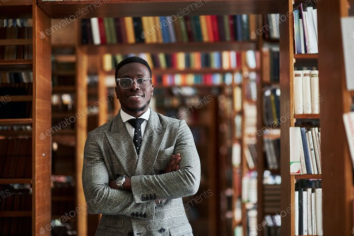 An African American man in a business suit standing in a library in the reading room