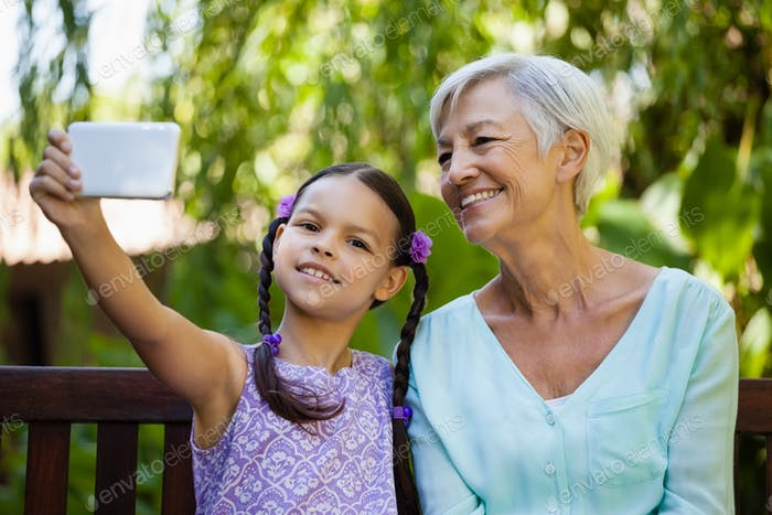 Smiling girl and grandmother taking selfie