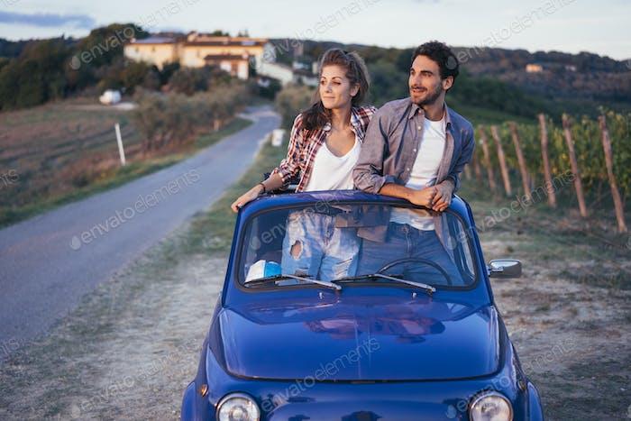 jóvenes pareja viaje con el coche de la vendimia