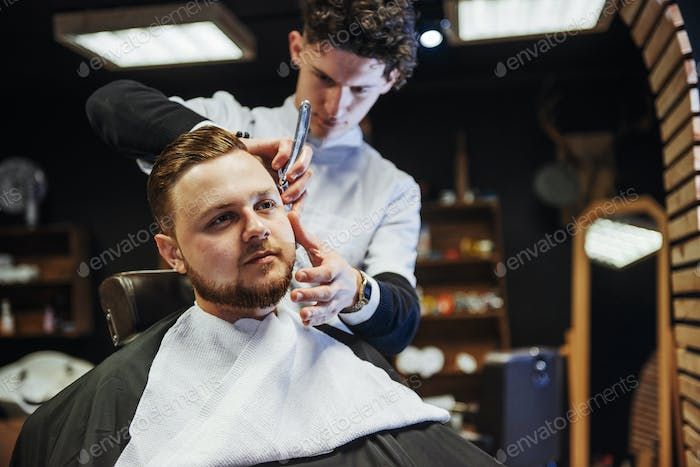 Man hairdresser doing haircut beard adult men in the men's hair salon