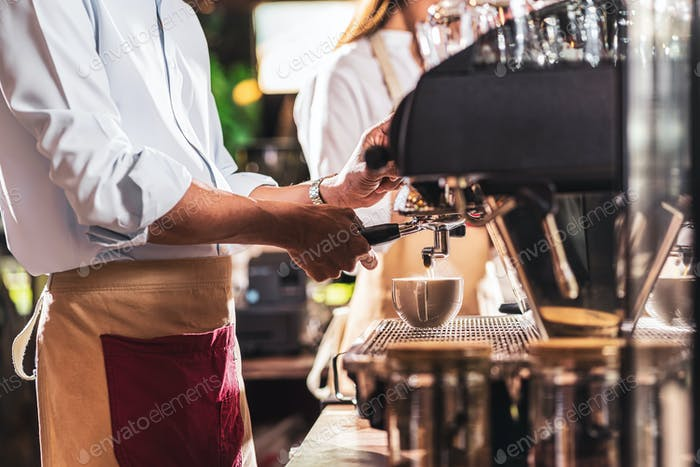 Asian Barista preparing cup of coffee, espresso with latte or cappuccino for customer order