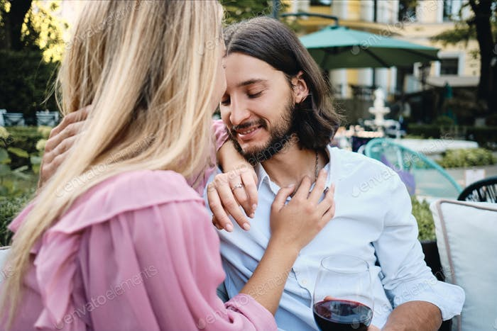 Attractive man with glass of wine dreamily hugging girlfriend on romantic date in restaurant outdoor