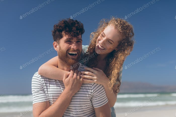 Romantic couple interacting with each other at beach on a sunny day. They are hugging each other