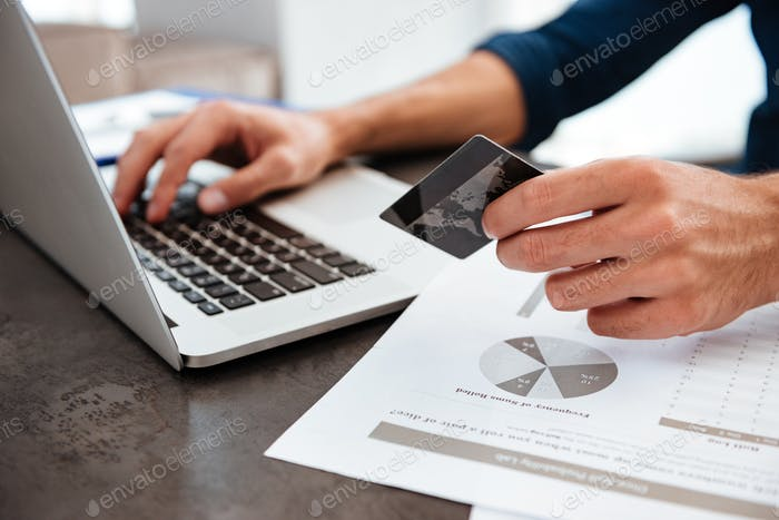 Cropped photo of young man holding credit card and typing