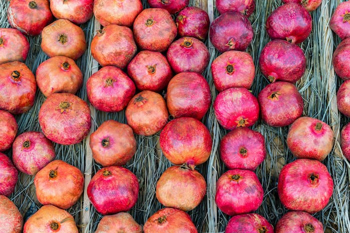 Close up of rows of pomegranates on a wooden counter lined with dry leaves