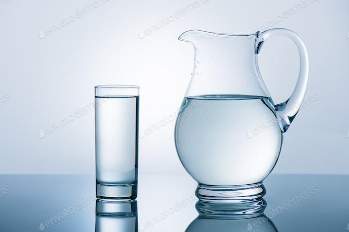Krug und Glas mit Wasser auf reflektierendem Tisch