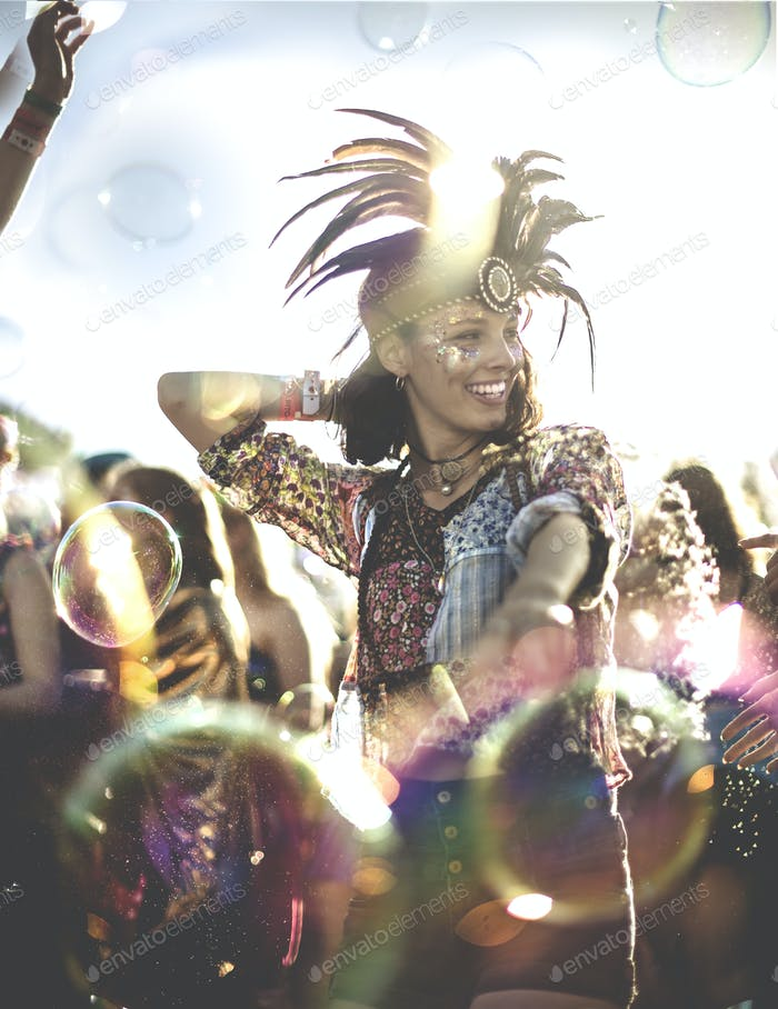Young woman at a summer music festival wearing feather headdress, dancing among the crowd.