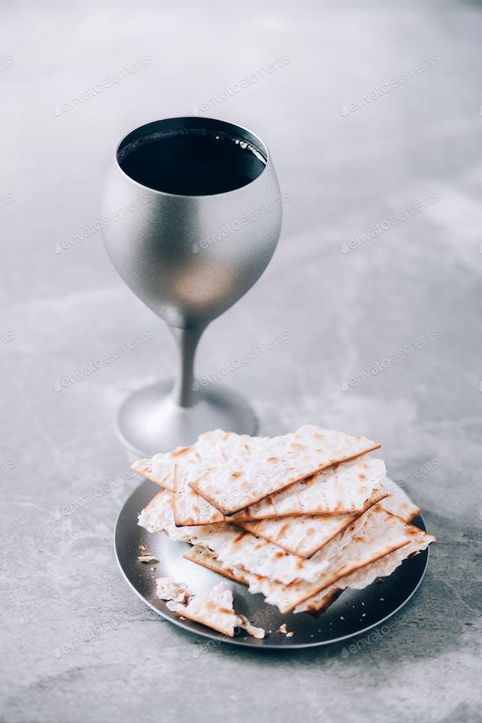 Kommunion Stillleben. Ungesäuertes Brot, Kelch Wein, Silber kiddush Weinbecher auf grauem Hintergrund