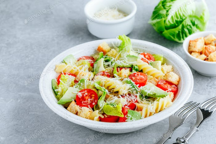 Fusilli pasta salad with avocado, tomatoes, fresh green lettuce, parmesan cheese and croutons