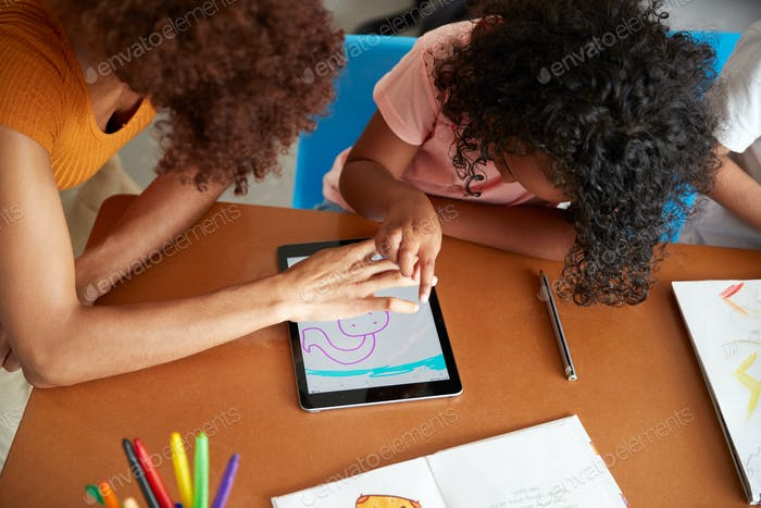 Elementary School Teacher And Female Pupil Drawing Using Digital Tablet In Classroom