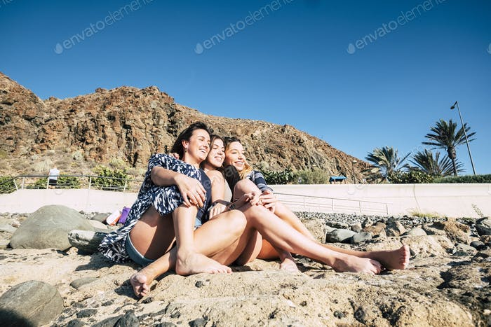 Three young beautiful woman sit down on the stones telling stories