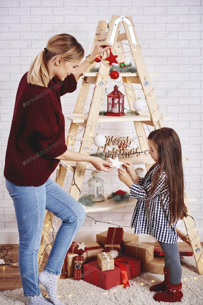 Mutter und Tochter schmücken den Weihnachtsbaum