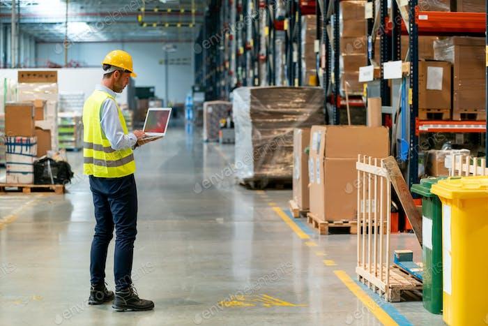 Менеджер склада проверяет инвентарь с ноутбуком, идущими между полками