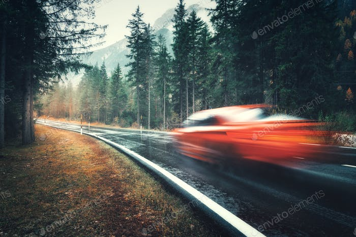 Blurred red car in motion on the road in autumn forest