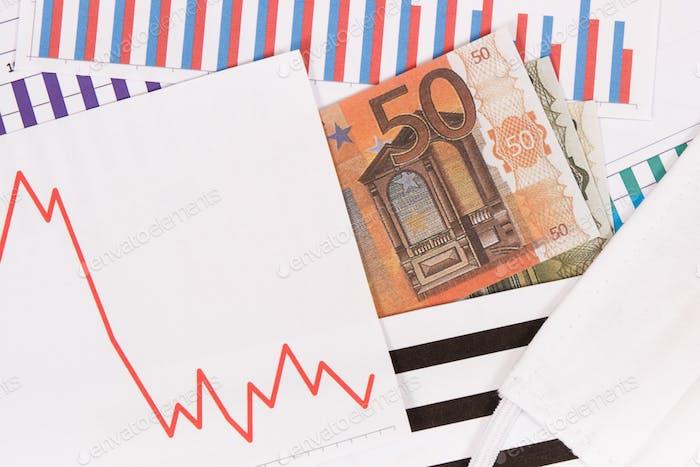Currencies euro and downward graphs representing financial crisis