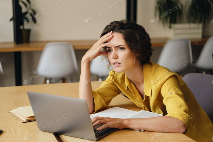 Young exhausted woman sitting at the desk with laptop tiredly holding hand near head at work