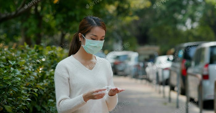 Woman use of hand sanitizer with face mask