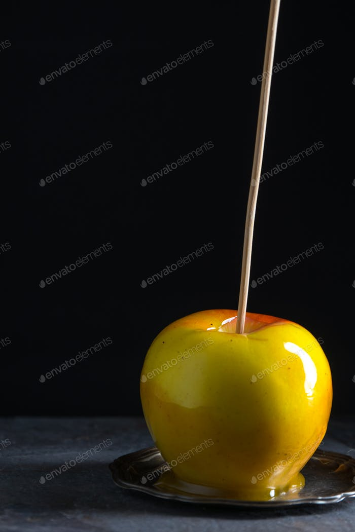 One caramel apple on a small tin plate