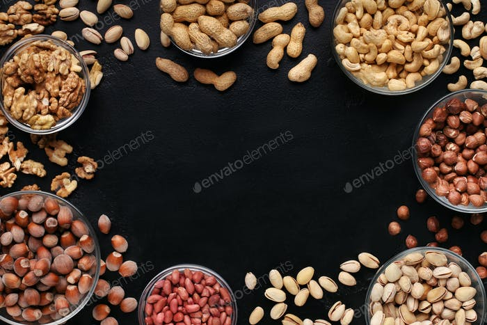 Frame of assorted nuts bowls on black background