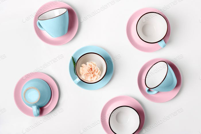 Elegant porcelain blue and pink cups on abstract background