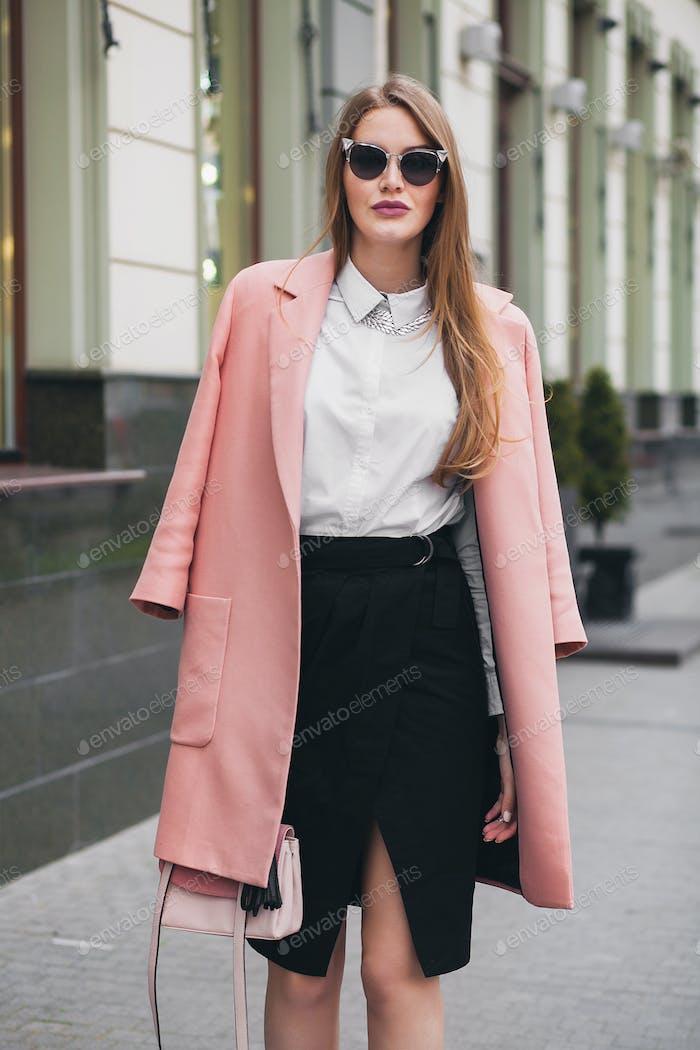 niedliche attraktive stilvolle lächelnde Frau zu Fuß Stadtstraße im rosa Mantel
