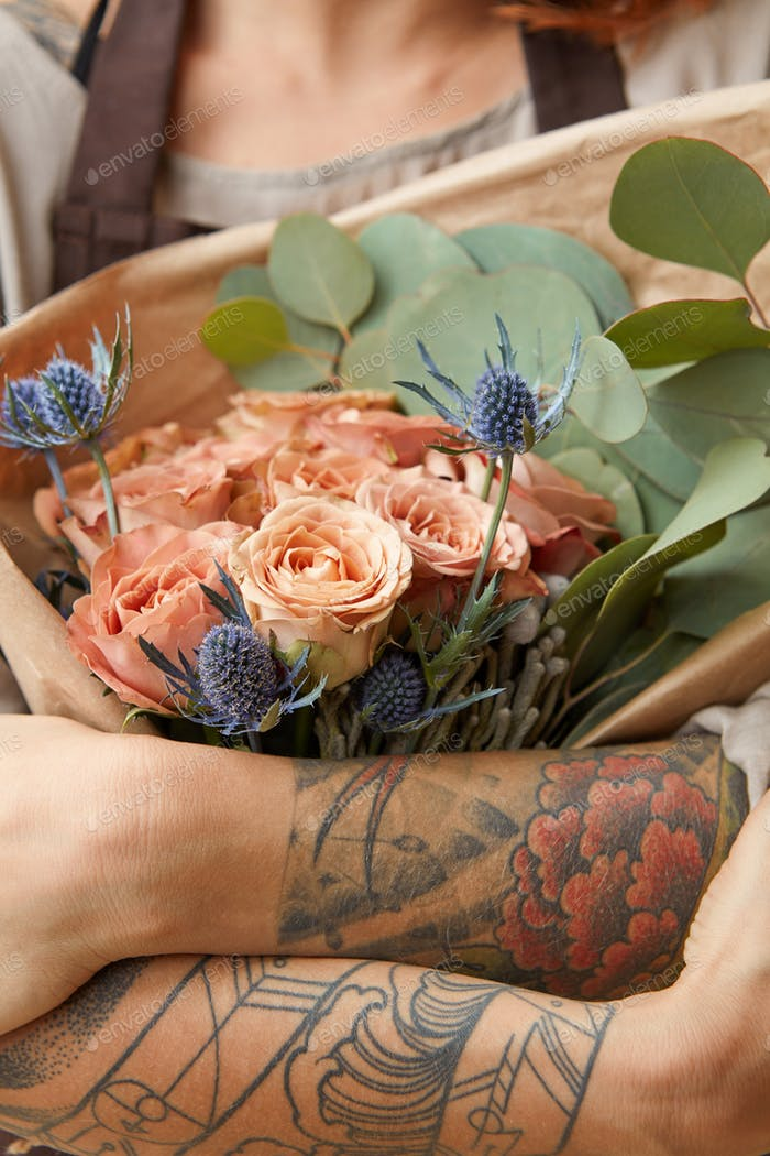 Close up of fresh tender roses and eryngium in a woman's hands with tattoo. Congratulation