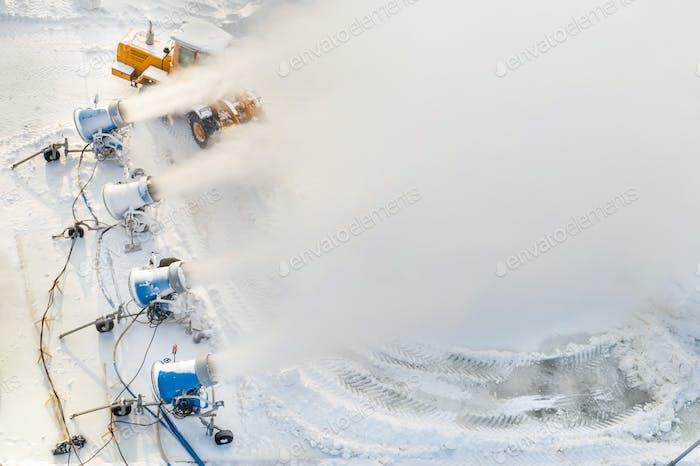 Blick von oben auf die Arbeit von vier Schneekanonen zur Herstellung von Kunstschnee