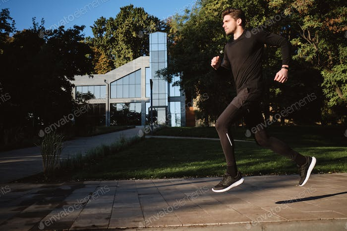 Young attractive stylish sporty man running in city park