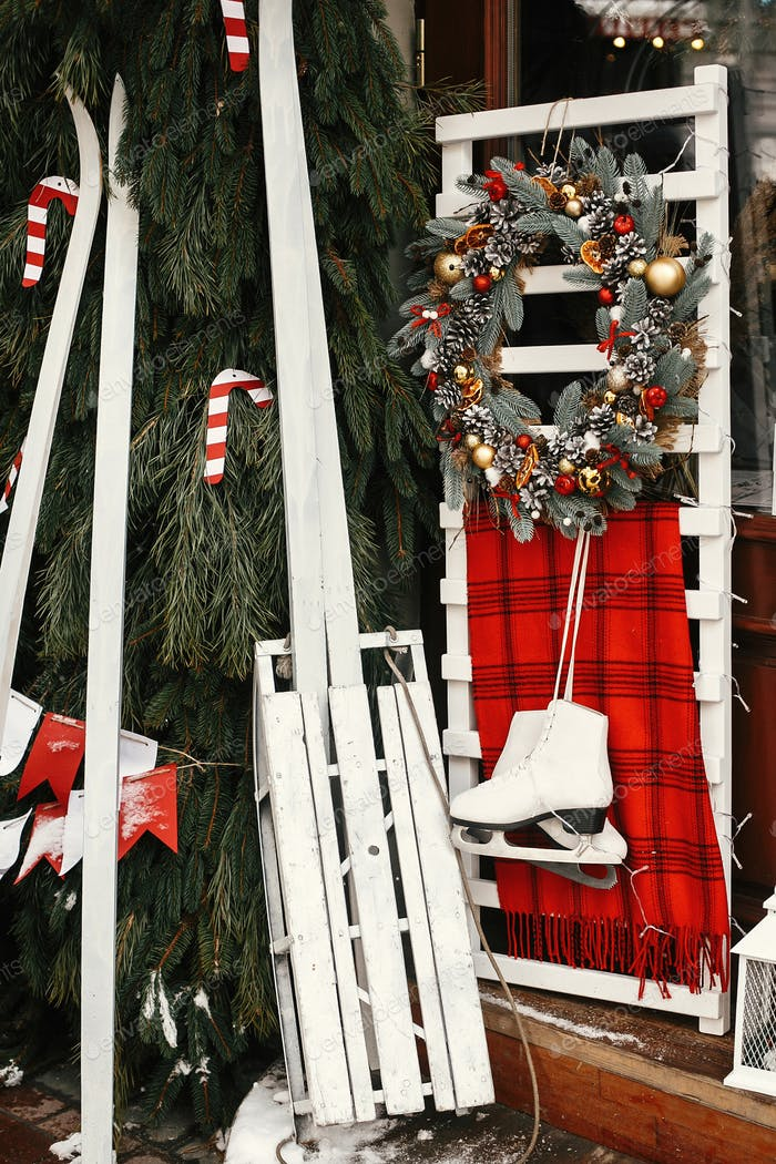Stilvoller Weihnachtskranz, weißer Holzschlitten und Schlittschuh