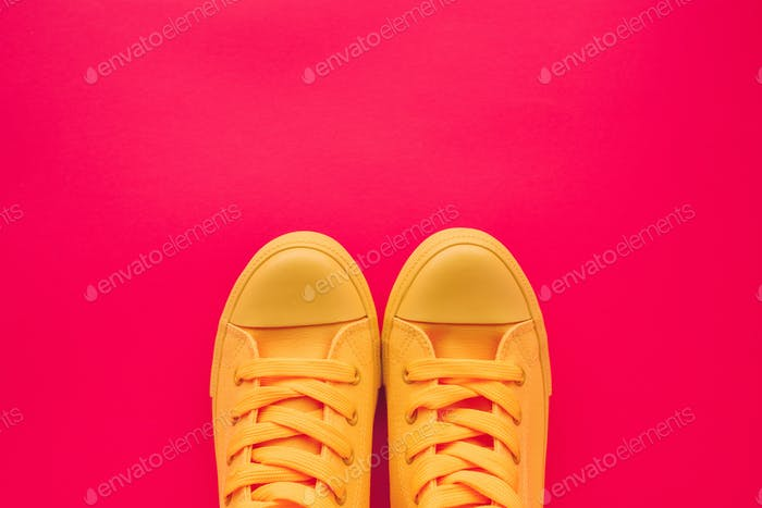 Yellow canvas shoes sneakers on neon pink background