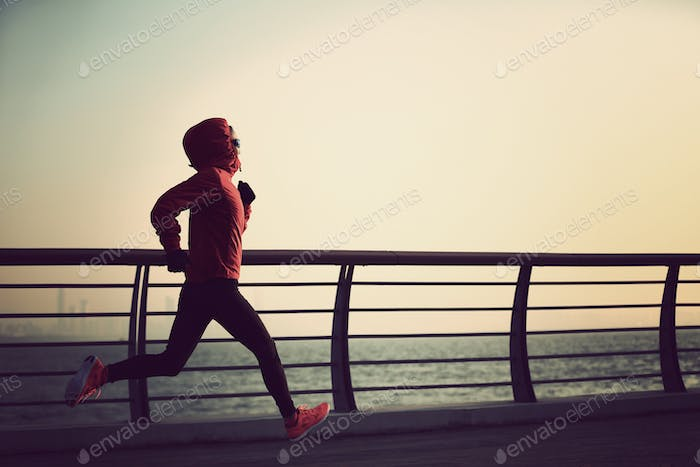 Young fitness woman runner running at winter seaside