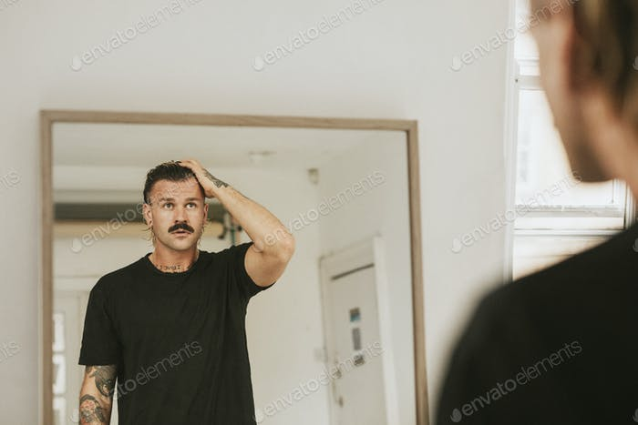 Fashionable man looking at himself in the mirror