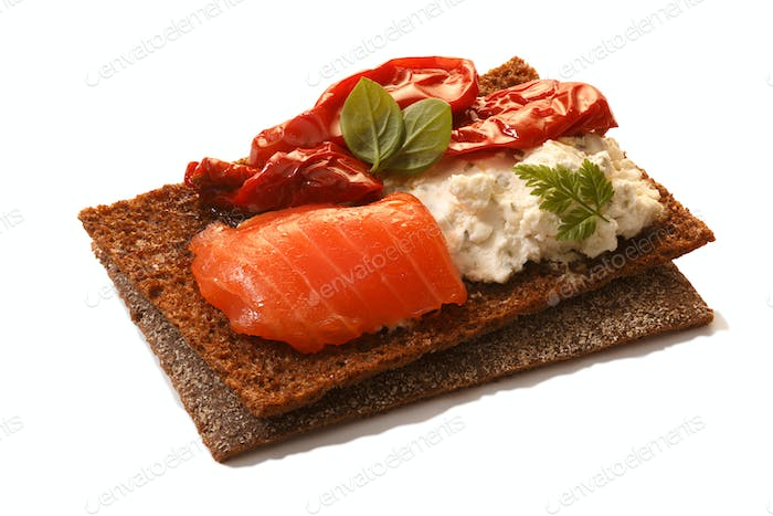 Bread crisp with salmon, soft cheese, dried tomatoes and chervil