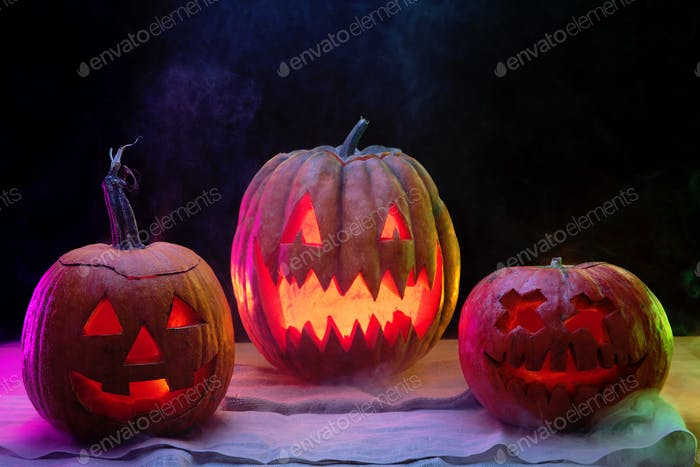 Halloween pumpkin head jack lantern with scary evil faces and candles